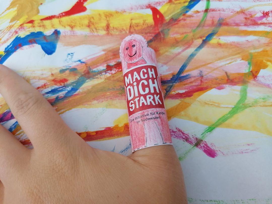 Daumen und Zeigefinger einer Hand vor einem bunten Kinderbild. Auf dem Daumen ist eine rote Puppe.