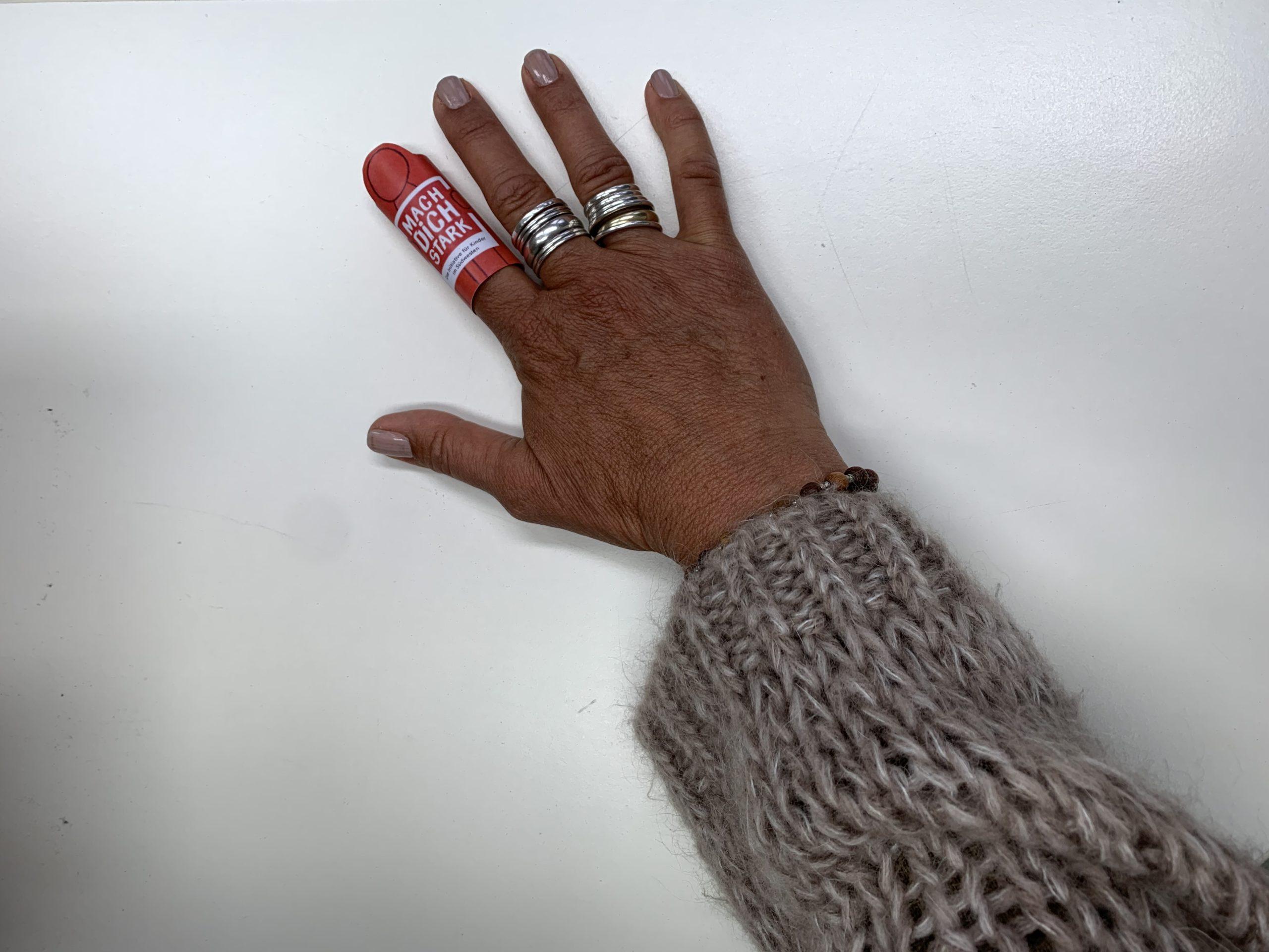 Eine Hand mit der Starkmacher-Fingerpuppe am Zeigefinger. Die Fingerpuppe ist eine rote Figur mit der Aufschrift MACH DICH STARK
