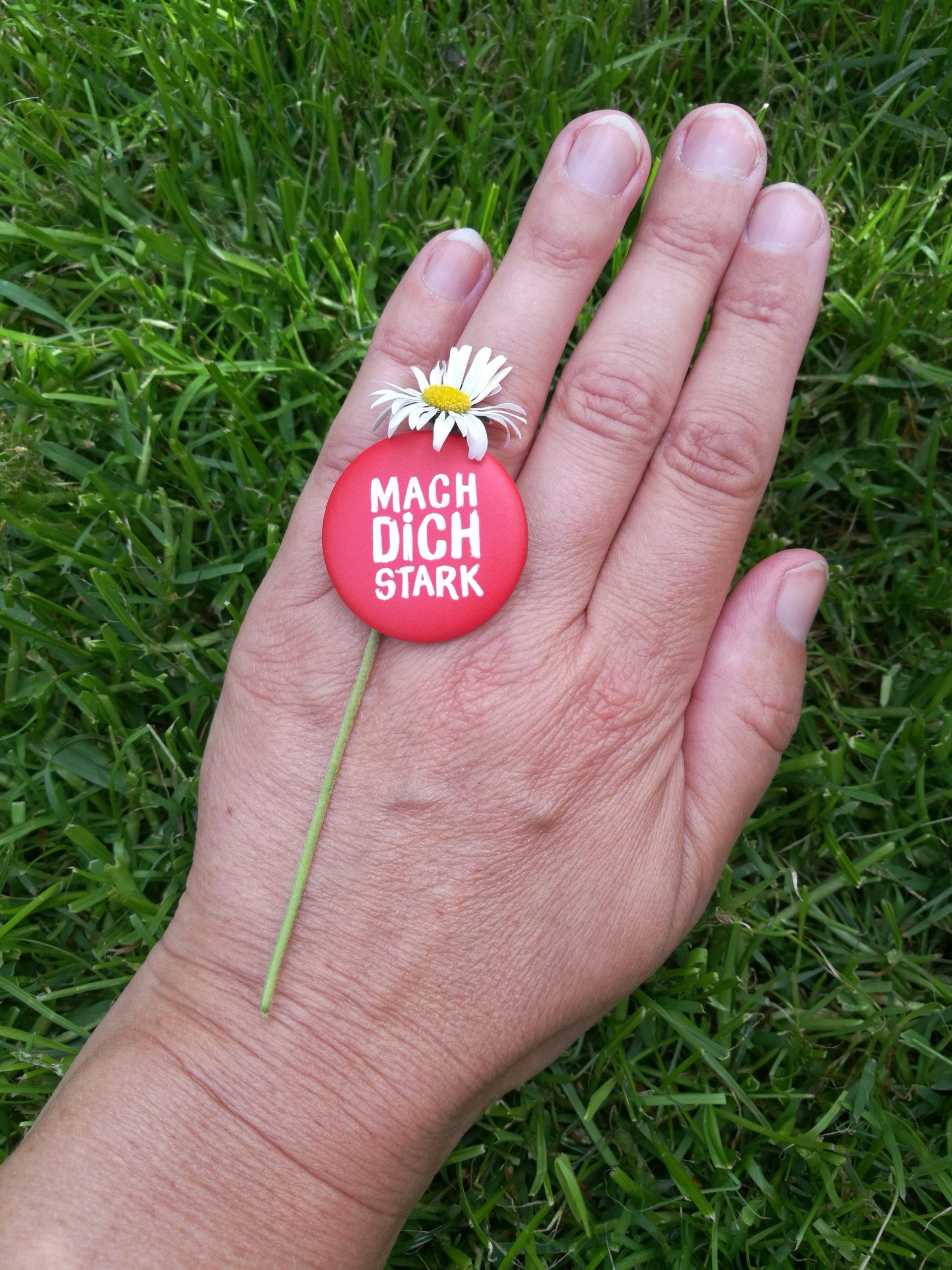 Eine Hand auf einer Wiese. Auf der Hand liegt ein Gänseblümchen mit einem Button.