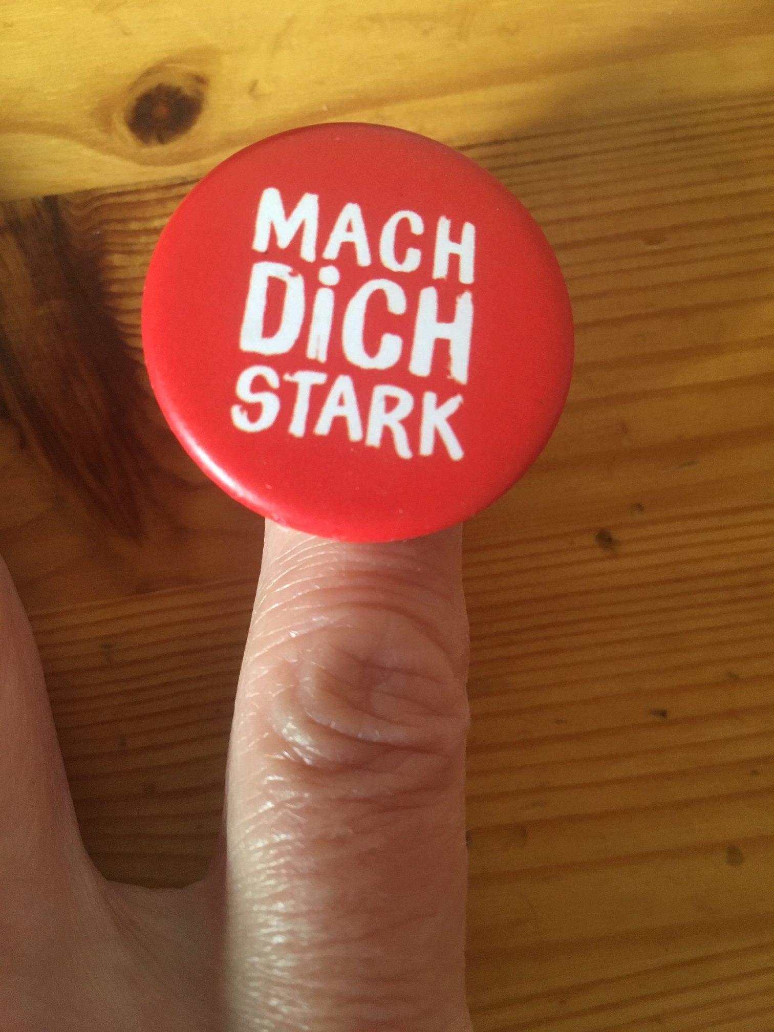 Der Zeigefinger einer Hand mit einem runden, roten Button. Im Hintergrund ein Holztisch.
