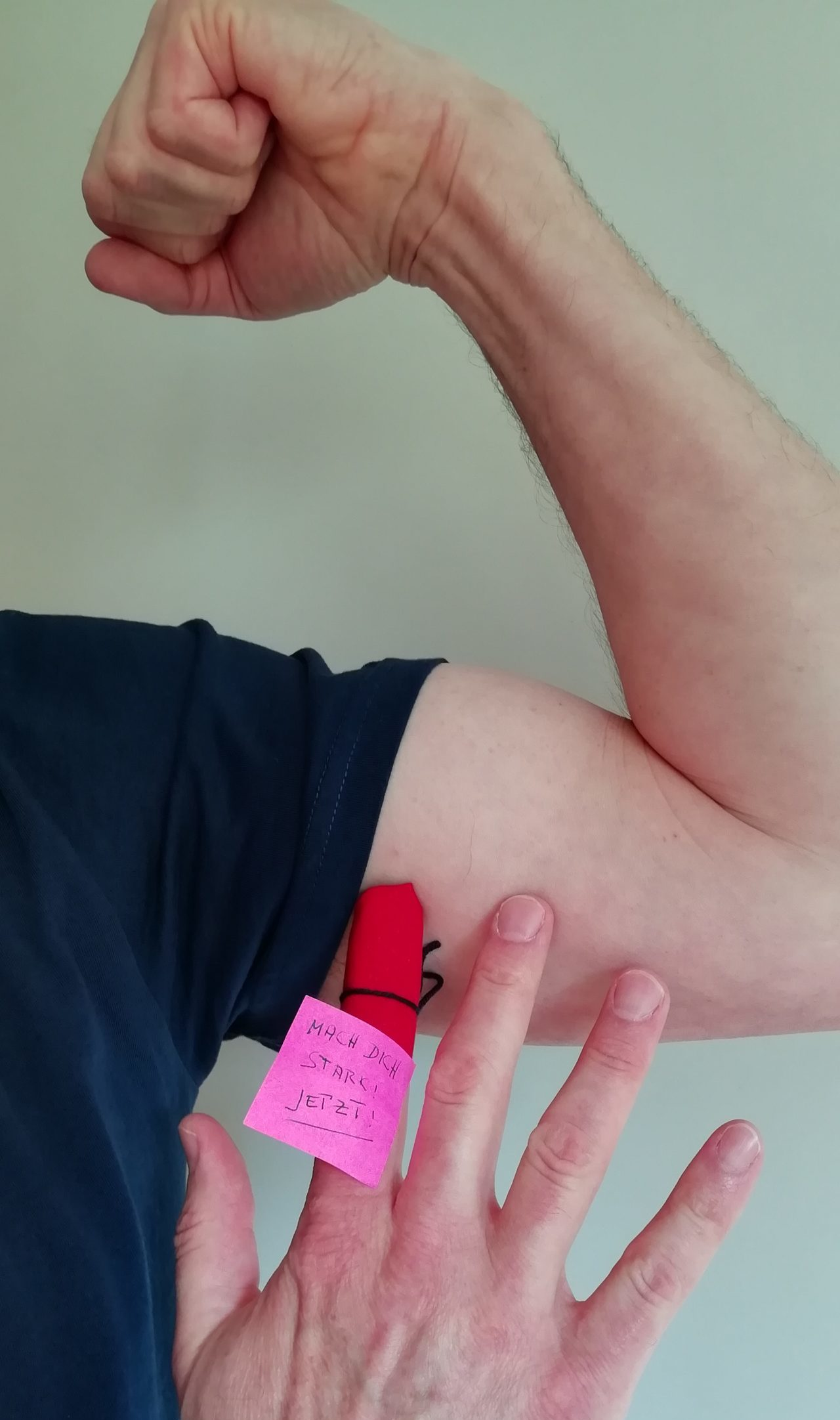 Ein Männerarm im rechten Winkel angespannt. Davor eine Hand mit einem roten Zettel. Die Aufschrift lautet: MACH DICH STARK - Jetzt!