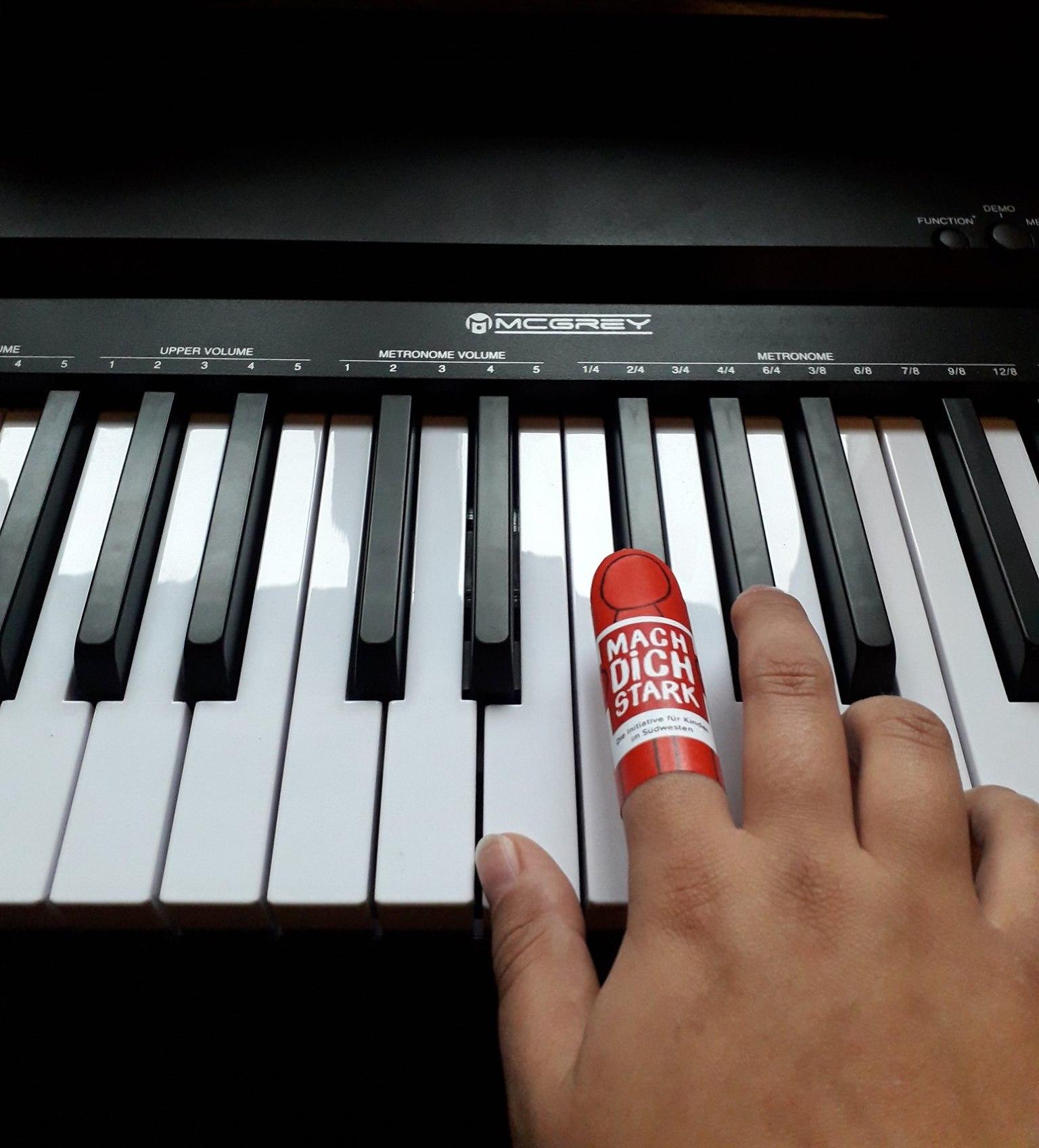 Eine Hand auf einer Klaviertastatur. Auf dem Zeigefinger der Hand ist eine rote Fingerpuppe.